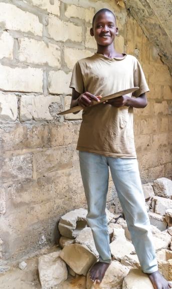 Un grand talibé avec, en main, une planche de textes coraniques